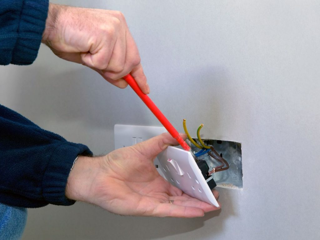 Electrician installing plug socket